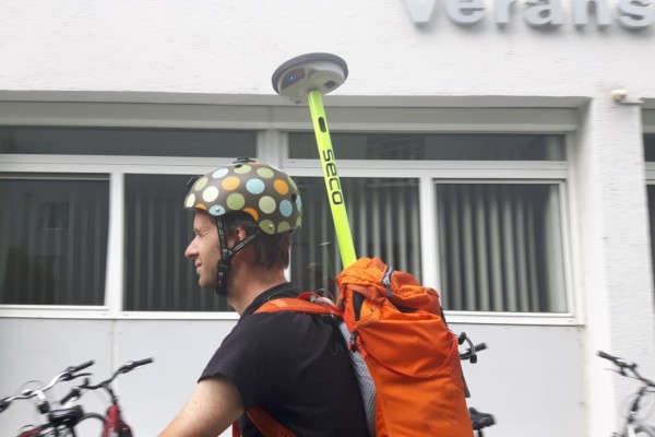 Cyclist with Leica'a GPS antenna attached to the backpack